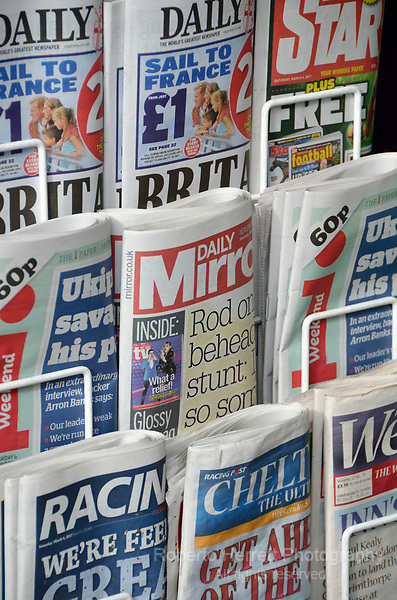 Various UK tabloid newspapers on a newsstand.