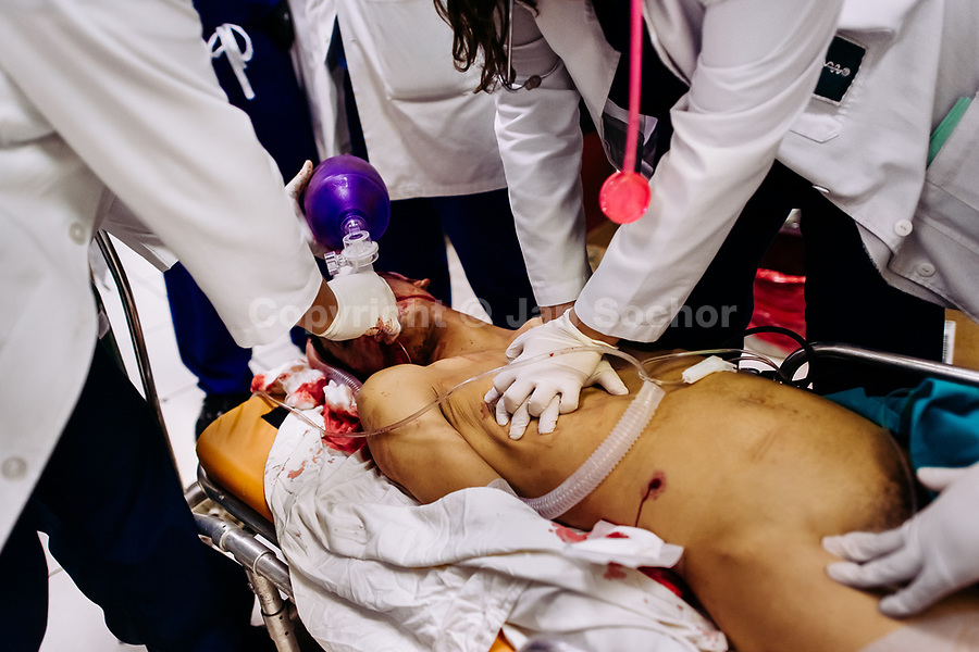 Emergency physicians provide a cardiopulmonary resuscitation to a young gang member, with an abdominal gunshot wound, in the emergency department of a public hospital in San Salvador, El Salvador, 16 December 2015.