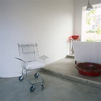 An old shopping trolley has been upcycled into a novel chair. It stands in a room with white walls and a concrete floor.