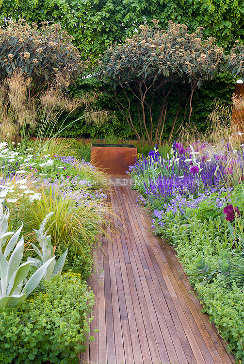 Garden Path Made Of Wood, Leading To Garden Water Feature, Lined With  Flowers And