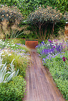 Garden path made of wood, leading to garden water feature, lined with flowers and groundcovers, ornamental grasses, shrubs, privacy hedge, in gorgeous garden design