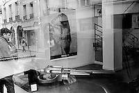 France. Ile-de-france Department. Paris. Art gallery. A woman looks through the window at a giant hand gun on the ground and a painting of a naked woman hanged on the wall. A man with a cap walks in the street. 22.02.05 © 2005 Didier Ruef