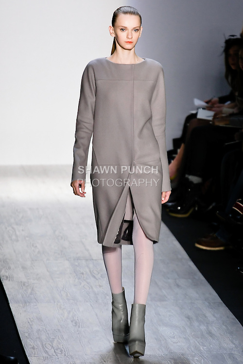 Tetyana Melnychuk walks the runway in a gray wool felt coat, bray silk goeorgette dress, gray tights, and gray platform boot, by designer Max Azria for the Max Azria Fall 2010 collection fashion show, during Mercedes-Benz Fashion Week Fall 2010.