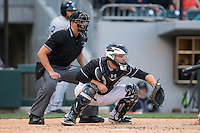 Charlotte Knights catcher Jeremy Dowdy (14) sets a target as home plate umpire Shane Livensparger looks on during the International League game against the Columbus Clippers at BB&T BallPark on May 27, 2015 in Charlotte, North Carolina.  The Clippers defeated the Knights 9-3.  (Brian Westerholt/Four Seam Images)