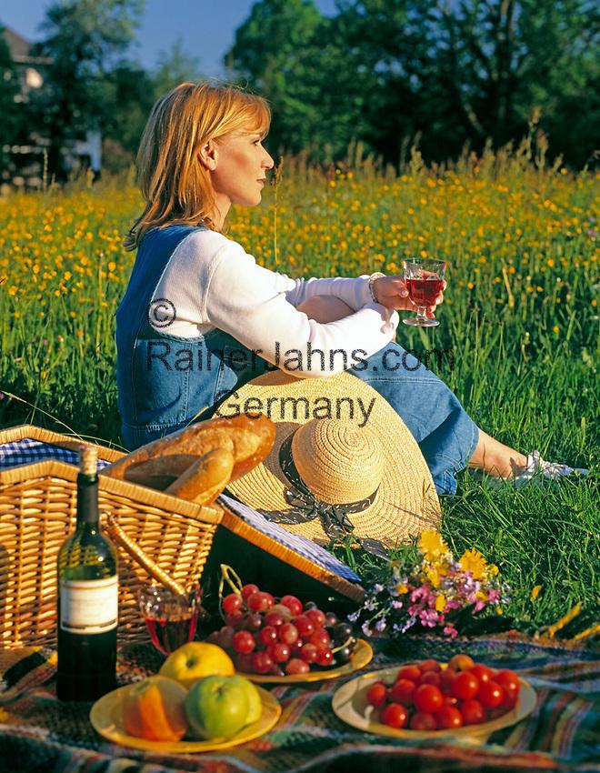Junge Frau beim Picknick in einer Blumenwiese, allein, nachdenklich | young woman having a picnic in a flower meadow, single