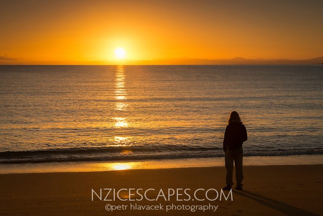 Woman watching sunrise from golden beach in Totaranui, Abel Tasman National Park, Nelson Region, New Zealand