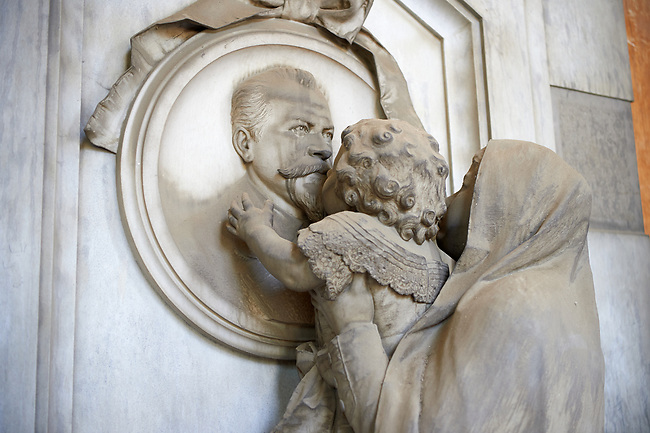 Picture and image  of the stone sculpture of a child being lifted to kiss the deceased.  The Casella tomb sculptor G Benetti 1884. Section A, no 40, monumental tombs of the Staglieno Monumental Cemetery, Genoa, Italy