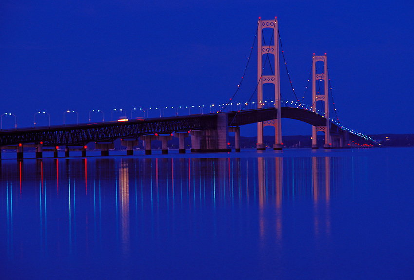 THE MACKINAC BRIDGE AND REFLECTING LIGHTS AT NIGHT, ST. IGNACE, MICHIGAN.