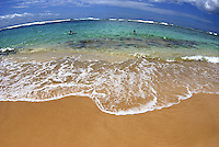 Haena shoreline, Tunnels Beach, a gentle wave washes ashore, Kauai