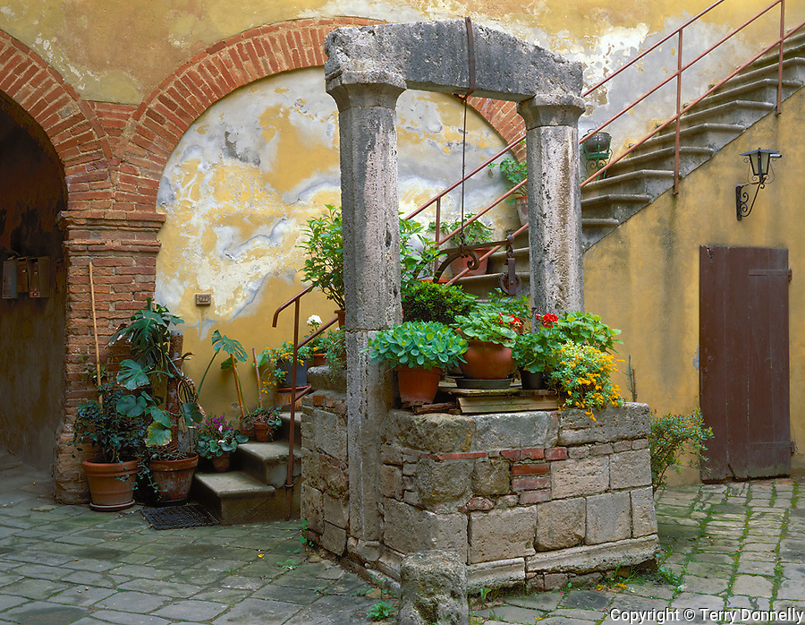 Stone well and stairs with potted flowers in a courtyard of the hill town of San Querico d'Orcia,<br /> Tuscany, Italy