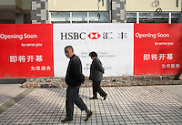 Pedestrians walk past a soon to be opened first branch of HSBC Rural Bank in Suizhou, China..