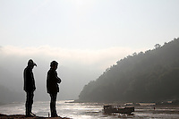 Two men are watching the boats passing by at Pak Beng, a commercial town between Houa Xai and Luang Prabang, Laos-2010