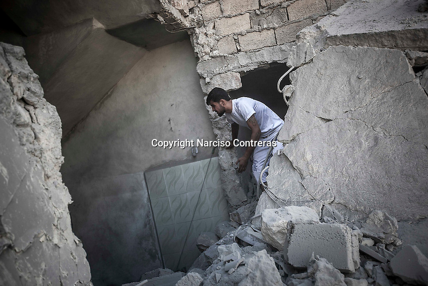 A Syria civilian walks among the debris of a demolished house building as he looks for the victims of an aircraft shelling just some minutes after the house was targeted by one army plane at Tarik Albab neighborhood in the northeastern of Aleppo City. The Syrian army is carrying out aircraft shellings over residential areas throughout Aleppo City, killing hundreds of civilians in its attempt to sweep out the rebels.