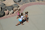 Three young girls in swimsuits running on a sidewalk in Denver, Colorado. .  John offers private photo tours in Denver, Boulder and throughout Colorado. Year-round Colorado photo tours.