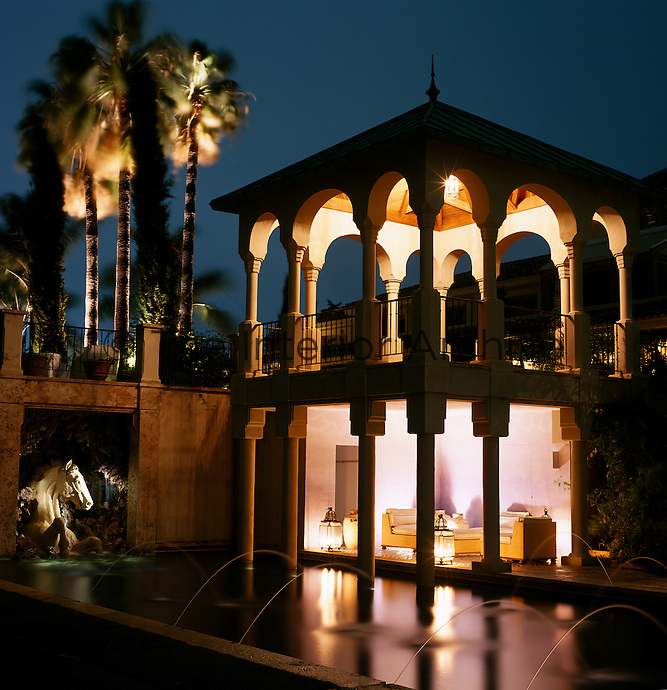 This double height garden pavilion is lit with lanterns, the light reflected in the waters of the fountain