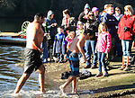 A father and son comes ashore after jumping off the bridge into the Burley Lagoon during the 31st annual Polar Bear on January 1, 2015 in Olalla, Washington. Over 500 hardy participants joined in on the annual New Year's Day Tradition by jumping into the chilly lagoon waters during the annual Polar Bear Plunge.  ©2015.  Jim Bryant Photo. All Rights Reserved.