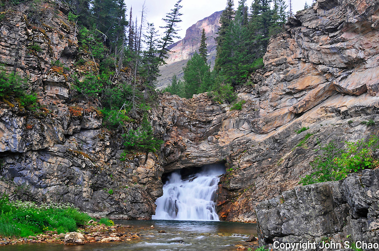 Running Eagle Falls, regarded sacred by native Blackfoot Indians and named in honor of a woman warrior, Pitamakan, appears to flow out of rock in Glacier National Park, Montana.