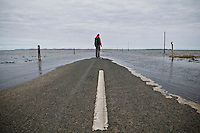 Woman stands on flooding road to Lindisfarne - Holy Island as high tide approaches, Lindisfarne, England