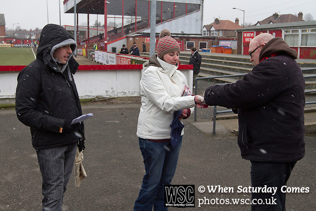 Altrincham 2 Worcester City 0, 23/03/2013. Moss Lane, Blue Square Bet North. A spectator buying a match day programme from vendors before the Blue Square Bet North fixture between Altrincham and Worcester City at Moss Lane, Altrincham. The home team won the match 2-0 watched by 777 spectators on a day when most non-League football in England was cancelled due to adverse weather. Altrincham were historically one of the major English non-League teams but have never been promoted to the Football League. Photo by Colin McPherson.
