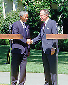 Washington, D.C. - June 25, 1990 -- United States President George H.W. Bush, right, shakes hands with Nelson Mandela, leader of the African National Congress (ANC), left, after welcoming the latter to the White House for talks on Monday, June 25, 1990.  This is Mandela's first visit to the United States following his release from Victor Verster Prison after 27 years in captivity..Credit: Ron Sachs / CNP