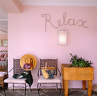"""A wrought-iron """"Relax"""" sign hangs above a pair of garden chairs and a butcher's block in this pink-painted garden room"""