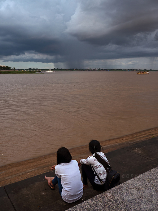 Monsoon Season in Phnom Penh. School children watching the rain storm over the Mekong. A heavy rainstorm over the Mekong River Cambodia