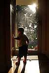 Sam Schurter, age two, stands in the doorway of his Springfield, Illinois home on a summer evening.