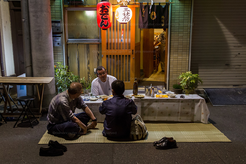 Festival goers enjoy a meal in the street on the evening of the last day of the Sanja matsuri, Asakusa, Tokyo, Japan. Sunday May 21st 2017 . The Sanja matsuri (Three shrines festival) is one of the biggest Shinto festivals in Japan. It takes place for 3 days around the third weekend of May and features over 100 large and small mikoshi, or portable shrines, which are paraded around the streets of the historic Asakusa district in Tokyo. to bring blessings and good luck on the inhabitants. The events attracts up to 2 million visitors each year.