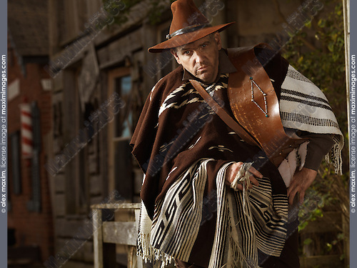 Cowboy sitting on a handrail with old wooden houses in the background