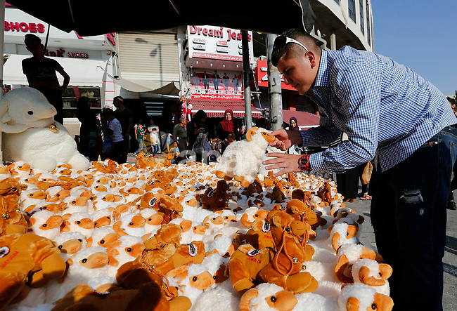 A Palestinian vendor displays toys of sheep at a market ahead of the Eid al-Adha festival in the West Bank city of Hebron, on August 21, 2017. Photo by Wisam Hashlamoun
