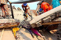 Rescue workers use steel cutting equipment to cut their way through parts of the collapsed Rana Plaza complex in Savar. The legs of two women crushed to death underneath the rubble are visible below. The 8 storey building, which housed a number of garment factories employing over 3,000 workers, collapsed on 24 April 2013. By 29 April, at least 380 were known to have died while hundreds remained missing. Workers who were worried about going to work in the building when they noticed cracks in the walls were told not to worry by the building's owner, Mohammed Sohel Rana, who is a member of the ruling Awami League's youth front. He fled his home and tried to escape to neighbouring India after the building collapsed but was caught by police and brought back to Dhaka. Some of the factories working in the Rana Plaza building produce cheap clothes for various European retailers including Primark in the UK and Mango, a Spanish label. . /Felix Features