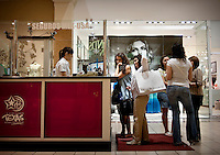 People line up at a money exchange to convert Mexican pesos into US dollars at La Plaza Mall in McAllen, Texas, Saturday, April 3, 2010. Trade with Mexico is flourishing in this town despite the spike in drug-related violence south of the border. While the State Department issues travel warnings to nearby Mexican cities, the number of good-laden trucks that crosses into McAllen is growing, as is trade-related investment. ...PHOTO/ Matt Nager