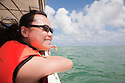 A mid adult woman enjoying a boat ride from Sandakan to Selingan Island (Turtle Island). Malaysia