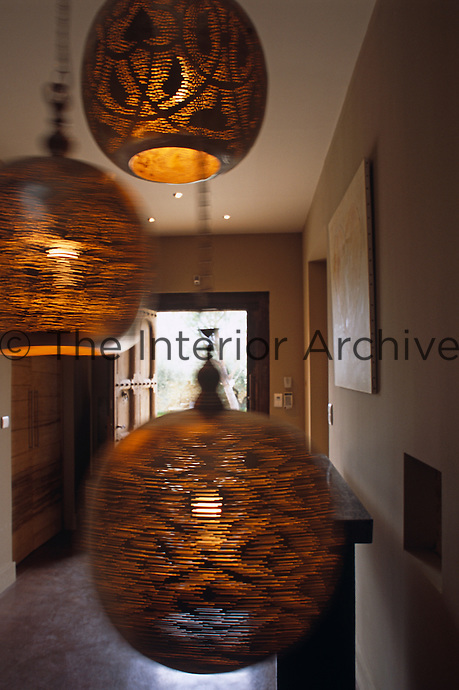 Three pendant lights in the entrance hall sway gently in a breeze through the open door