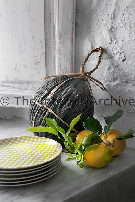 Freshly picked lemons and a melon ripen on the marble window sill