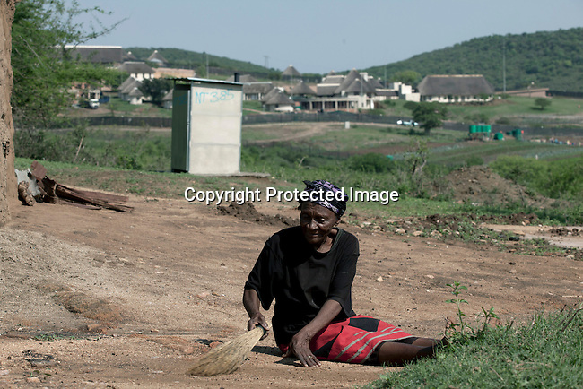 NKANDLA, SOUTH AFRICA - OCTOBER 10: An elderly woman sweeps outside her one-roomed mud house next to the new home for South Africa president Jacob Zuma's in his birth village on October 10, 2012 in KwaNxamalala, Nkandla. South Africa.  The South African government is spending R240-million (about US$ 27 million) to construct the vast property for his large family. (Photo by Per-Anders Pettersson)