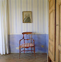 The walls of the dining room have been painted in blue and white stripes to mimic old-fashioned wallpaper