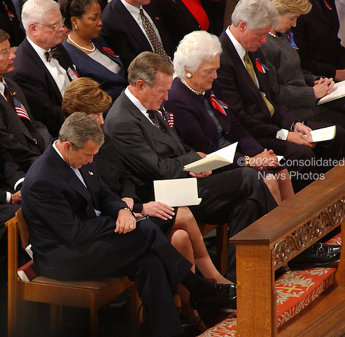 United States President George W. Bush bows his head in prayer during the National Day of Prayer Service at the Washington National Cathedral in Washington, D.C. on Friday, September 14, 2001.  Left to right across the photo are U.S. President George W. Bush, First Lady Laura Bush, former President George H.W. Bush, former First Lady Barbara Bush, former President Bill Clinton, and U.S. Senator Hillary Rodham Clinton (Democrat of New York).Credit: Ron Sachs / CNP
