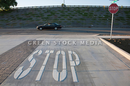 A 'STOP' road marking and a Stop sign at an intersection, a car passing by in the background.  Mountain View, California, USA