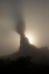 Sunrise behind Balanced Rock in  fog in Arches National Park near Moab, Utah, USA, produces an eerie shadow.