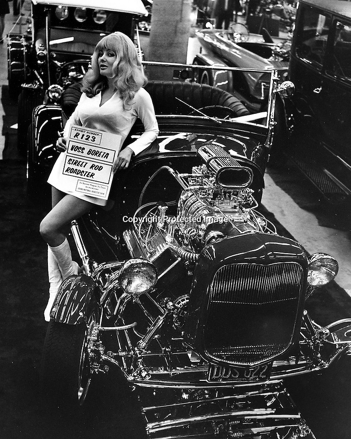 topless star Carol Doda at the Roadster show holding Voss Boretta sign with his roadster. (photo/RonRiesterer)