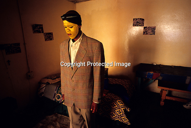 Luxolo Mkwelo, age 19, stands in his room after coming home from a traditional manhood ceremony on August 20, 2000 in Tshatshu, South Africa. He spent six weeks in the bush learning to be a man. He was circumcised and elders guided him during the ceremony, which is to prepare them for adulthood. Former South African president Nelson Mandela went trough the ceremony when he was young.