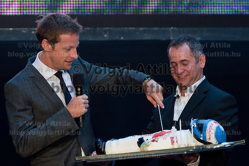 McLaren Formula One driver Jenson Button (L) of Britain cuts a F1 driver shaped cake on stage during the annual Hugo Boss party just prior to the Hungarian F1 Grand Prix in Budapest, Hungary. Thursday, 28. July 2011. ATTILA VOLGYI