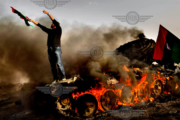 A man waving a pre-Gadaffi era Libyan flag stands on a burning tank that had been a part of the pro-Gadaffi forces attacking Ajdabiya. On 17 February 2011, an uprising against the 41 year rule of Col. Muammar Gadaffi started in eastern Libya..