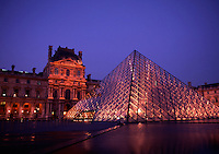 The glass pyramid and exterior view of the Louvre Museum at night. Paris, France.