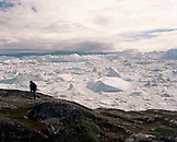 GREENLAND, Ilulissat, Ilullisat Icefjord, woman walking with glaciers in the background