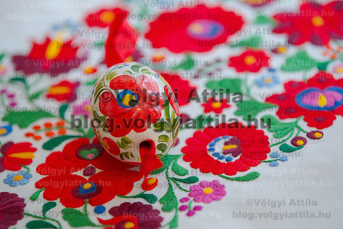 Painted egg lies on a traditional Matyo embrodiery in Mezokovesd, Hungary on April 5, 2012. ATTILA VOLGYI