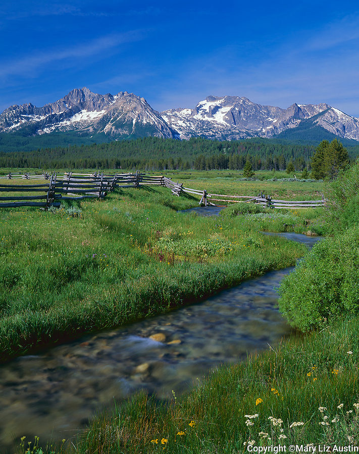 Sawtooth NRA, ID: Small stream and wood rail fence cuts through a grassy meadow with peaks of the Sawtooth Range in the distance