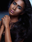 Expressive emotional beauty portrait of a young woman with dark skin and natural long brown hair on dark blue background