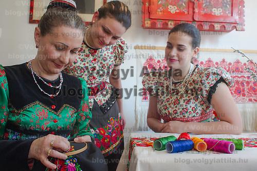 Girls watch as a woman sews traditional Matyo embrodiery in Mezokovesd, Hungary on April 5, 2012. ATTILA VOLGYI